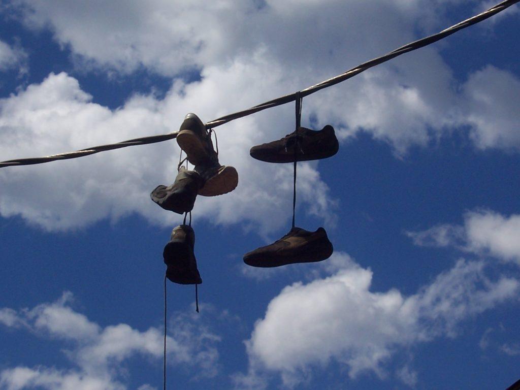 Drei Paar Schuhe über einem Kabel